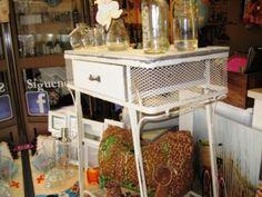 Mueble de estilo vintage blanco de madera, hierro y rejilla. Tiene un cajón y base que sirve de balda.
