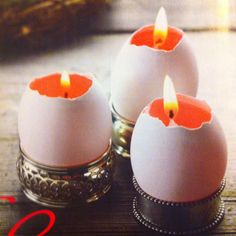 Homemade egg candles. Chatelaine April 2012. Melted wax poured into the bottom and then a birthday candle cut to fit is inserted inside. They are resting on metal napkin rings.