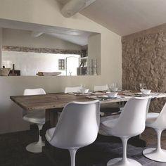 Une cuisine semi-ouverte sur la salle à manger de cette bâtisse en pierre…