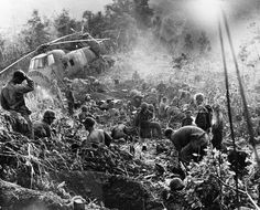 Weary after a third night of fighting against North Vietnamese troops, U.S. Marines crawl from foxholes located south of the demilitarized zone (DMZ) in Vietnam, 1966. The helicopter at left was shot down when it came in to resupply the unit.
