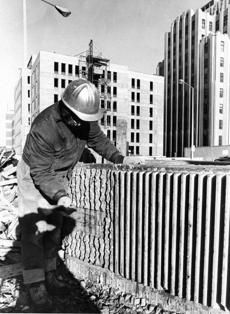 Rudolph used a technique in his building referred to as corduroy concrete, here a worker creates this effect by using a mallet on the freshly poured ribbed concrete