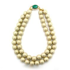Two strands of gilded wood beads (with an emerald green clasp) have all the refinement of traditional pearls, but a bit more zip.