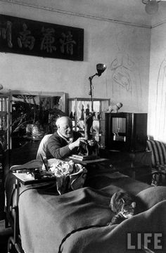 Henri Matisse sculpting in bed with his cat.