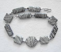 Gray Crazy Lace Agate and Gray Zebra by MoonbeamsLilacsRoses. Miriam combined a stunning round Gray Crazy Lace Agate, with square and oblong Gray Zebra Jaspers to create this distinctive necklace. The smaller Gray Zebra and Sterling Silver accents add a stylish touch to this elegant piece. The Sterling Silver S-shaped Clasp continues the design with its round, flat beaded design. Priced at $180.