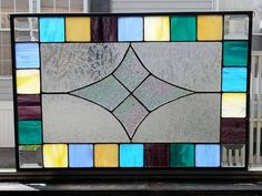 Stained glass window panel is made using an array of colors in wispy glass. yellow, blue, green, crème, cream, purple as well as (4) 2 lead crystal…