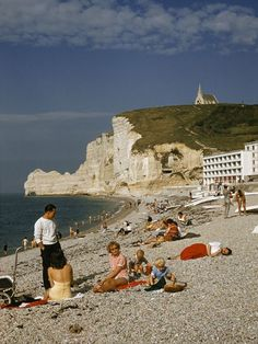 Etretat, France, 1959. Notre Dame de la Garde Chapel, located atop the chalk cliffs, provides a scenic backdrop for people lounging on the rocky beach in Etretat. Kodachrome photograph by Howell Walker, National Geographic