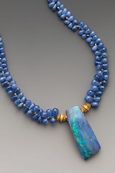 Your own personal lap pool...Australian boulder opal with characteristics of black opal on graduated faceted periwinkle blue tanzanite drops with 18K gold & diamond accents. 18K & diamond clasp