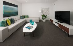 Modern media room with pops of colour. #mediaroom #livingroom #interiordesign #home #decor #design #blue #green #cornerlounge #cornersofa #wallart #artwork #white #endeavourfoundation #lotteries #prizehome