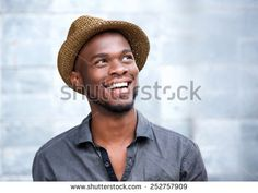 Close up portrait of a happy young african american man laughing against gray…