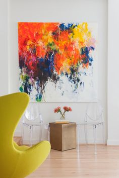 Two transparent chairs sit underneath a huge multicolor painting in this bright white modern sitting area. A small gold table is topped with a vase of flowers to bring out the colors in the painting. A modern egg chair in chartreuse is an eye-catching piece in this sleek space.