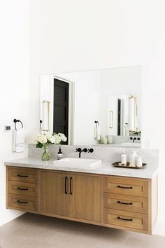 Modern bathroom with a floating wooden vanity, marble countertops, and flowers