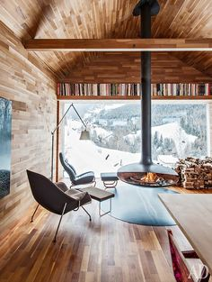A modern ski chalet with a floating fireplace, and floor to ceiling woods