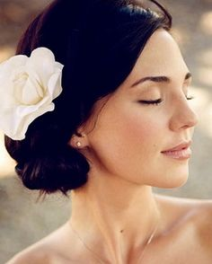 If you're looking for classy, simple, and a bit romantic, this is a lovely option -- natural, complementary makeup and a beautiful flower hairpiece in a low bun