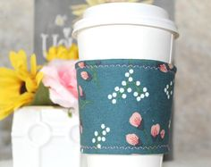 Coffee cozy measures about 10 inches across and 2.5 inches tall. It is created using high quality cotton fabric and has a batting middle to keep your beverages just right! Each coffee cozy features a button and elastic closure to wrap around your cup. It is pictured on a medium sized coffee in the listing but the elastic feature does allow for some stretch. Spot clean only, air dry, do not microwave. This reusable coffee cozy features a floral print, fall fabric and a metallic, gold button…