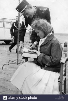 Download this stock image: Schneider, Romy, 23.9.1938 - 29.5.1982, German actress, half length, sitting, autographing, circa 1956, 1950s, man, uniform, hel - B486DM from Alamy's library of millions of high resolution stock photos, illustrations and vectors.