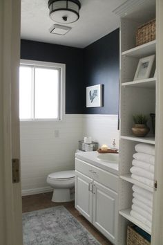 Navy Bathroom Decorating Ideas Simple, crisp white and navy bathroom. Blue wall paint, white vanity and open shelves - by Chris Loves Julia Bathroom Decor Navy Blue Bathroom Decor, Navy Blue Bathrooms, White Bathroom Paint, Small Bathroom, Bathroom Colors, Half Bathrooms, White Vanity Bathroom, Luxury Bathrooms, Bathroom Plants