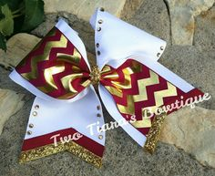 Maroon and gold foil chevron on white tick tocked with gold rhinestones and trimmed by Two Tiara's Bowtique on Etsy or Facebook as TwoTiaras Bowtique!  Great for Florida State University fans!  Teams, squads, state, competition, softball, pro shops!  FSU, Seminoles Check out this item in my Etsy shop https://www.etsy.com/listing/216865132/maroon-gold-chevron-tick-tock-cheer-bow
