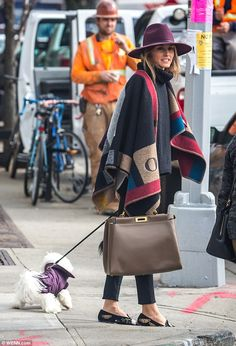 Winter chic: Under Olivia's colourful poncho, which was emblazoned with her initials, she wore a black knit sweater over black skinny jeans