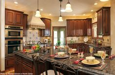 One of the bigger islands we have seen to go along with pendant lighting, a tiled backsplash and mahogany cabinets. Click on the image to see the kitchen trends you have to know in 2015.