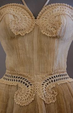Not a corset, but reminiscent of one in its architectural feel and detailing. Details of a Carven pleated, embroidered gown, circa 1950s.