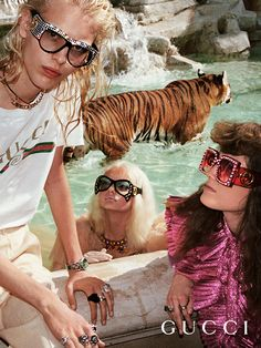 """Captured near a marble fountain in Rome, the Gucci Spring Summer 2017 campaign with printed t-shirt, fashion jewelry embellished by the phrase """"L'Aveugle Par Amour"""" and the Gucci Hollywood Forever eyewear collection with inverted cat-eye frames and giant GG interlocking logo on the temples."""