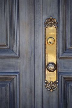 Hardware Idea: Doorknob with radial leaf design on long, scrollwork-ended brass face plate and deadbolt on distressed silver-blue door. This pin is for a T-shirt bearing this image, from www.inkity.com.