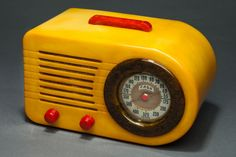 """Extremely Rare + Beautiful all original Art Deco FADA """"All-American"""" Bullet Streamliner Series 200 with a yellow cabinet, marbleized blue dial bezel + bright red marbleized Catalin handle and knobs. This radio styling epitomizes 1940's Streamline design. Its sleek, rounded lines suggest speed and practicality, hallmarks of streamlined industrial design from those years."""