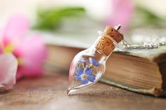 A tiny bunch of forget me nots, a token from of the first days of summer have been preserved and captured a tiny glass vial to make this dainty little botanical necklace. A traditional symbol of love and devotion this teardrop pendant would make such a romantic gift for a bride to be or (especially as her something blue) or other loved one! As a symbol of remembrance this would also be a lovely little reminder of someone special youd like to keep close to your heart.  Forgetmenots have…