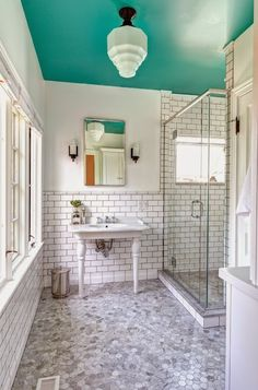 Incredible bathroom with teal painted ceiling adorned with a vintage style, semi flush mount pendant over a subway tiled half wall with black grout over marble hex bathroom floors.