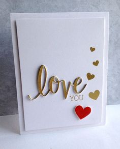 "Gold embossing powder on the die-cut ""love"" and stamped hearts looks great on this handmade white wedding card. Love the pop of red on one heart."