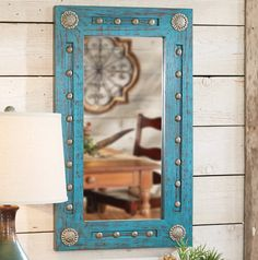 A bold antiqued turquoise finish is accented by silver conchos and hammered clavos on the handmade Turquoise Silver Trails Wood Mirror with a pine frame.