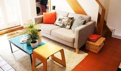 A grey sofa, blue coffee table, wooden side table, textured rug and printed cushions give a homely feel to Rick's room.