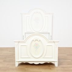 This cottage chic bed frame is featured in a solid wood with a white paint finish. This twin sized bed has intricate carved trim, curved edges and oval inset panels with pastel painted flowers. Adorable bed perfect for a kids room! #shabbychic #beds #headboard&footboard #sandiegovintage #vintagefurniture