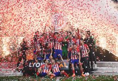 Torres lifts the Europa League trophy for Atletico as the players celebrate their victory ...
