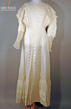 An ecru-coloured cambric dress with lace insertions, embroidery work, and find tucks. The dress fastens at the back with eight white buttons and three dome fasteners. Grey Roots Museum & Archives Collection.