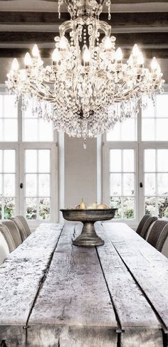 A great look for your summerhouse with an elegant chandelier over a rustic farmhouse dining table