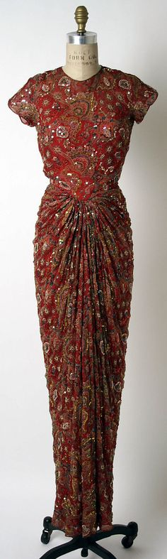 Evening dress by American designer James Galanos  (born Philadelphia, Pennsylvania, 1924).  Fall/winter 1957–58. Constructed of silk, synthetic pearl, and plastic.  In the collection of The @Metropolitan Museum of Art