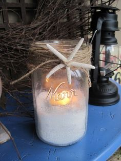 Mason jar candle with sand, starfish, and twine.