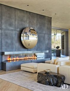 A mirrored Anish Kapoor sculpture animates the living room's blackened-steel fireplace surround