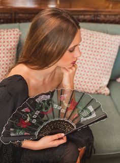 Black Hand-embroidered fan with colorful thread n a floral pattern, with slats made from semi-hard lacquered wood. http://capricesspanishartists.com/en/product/hand-fan-black-and-colour/