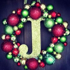 ornaments, a styrofoam wreath, a glue gun, a wooden letter and glitter are ALL you need to make this