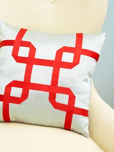 Light blue pillow with red grosgrain ribbon design on top