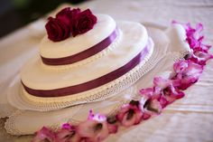 The Wedding Cake decorated with red flowers and burgundy ribbons