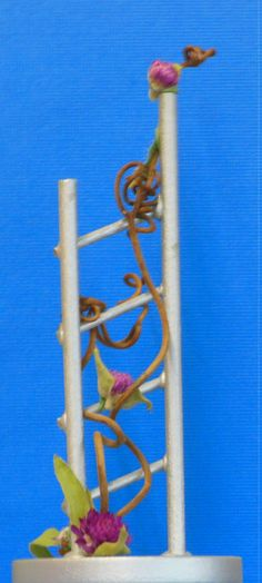 """Pathfinder"" by Jan Krass. This 5"" miniature floral design uses a structure Marc and I made a couple years ago, with gomphrena and grapevine.  Blue ribbon @2015 Clay Co. Fair."