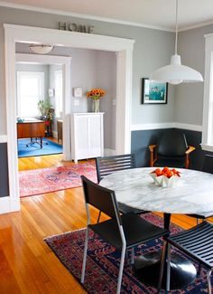 Two shades of gray in a dining room. Gray just meshes with pops of bright color like sunflowers and oranges.