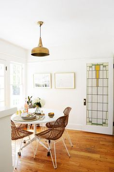 rattan dining dhairs around modern white table. / sfgirlbybay