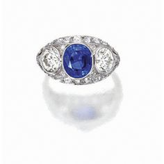 ART DECO SAPPHIRE AND DIAMOND RING, CIRCA 1920 Set in the centre with a cushion antique mixed-cut sapphire weighing approximately 3.27 carats, flanked by two circular-cut diamonds together weighing approximately 1.80 carats, framed by smaller similarly-shaped diamonds, mounted in platinum.