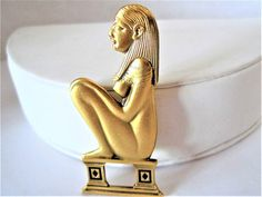 Egyptian Nefertiti Brooch, Signed RMA, Egyptian Revival, Gold Tone Pin  Offered by VintagObsessions, this Egyptian Nefertiti brooch features a naked Nefertiti in a sitting position. Unusual Egyptian Revival brooch ready to wear or to add to your collection. Hallmark: RMA - signed on