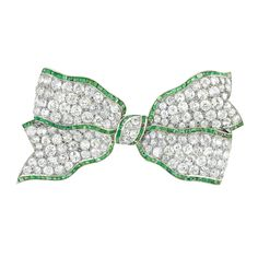 Art Deco Platinum, Diamond and Emerald Bow Brooch, France  18 kt., the cinched bow encrusted with 146 old-mine cut diamonds approximately 12.75 cts., edged by calibre-cut emeralds, no. 1626, with maker's mark and French assay marks, circa 1925, approximately 18 dwts.