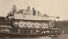 Tiger I traveling by rail. I'm guessing that this is an early production one, due to the panzer gray areas around the cross marking, indicating that it was repainted with panzer yellow. IIRC the panzergelb colour was adopted in mid-late 1942 .